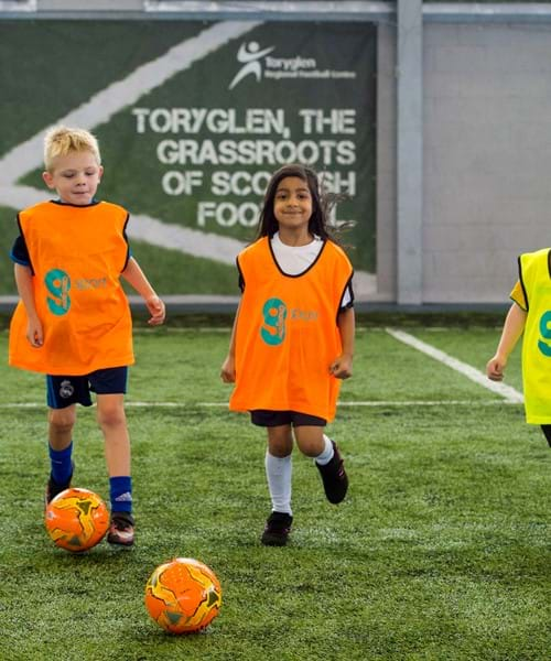 Children playing football wearing brightly coloured vests