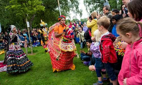 Children watching brightly coloured performers at Glasgow Mela