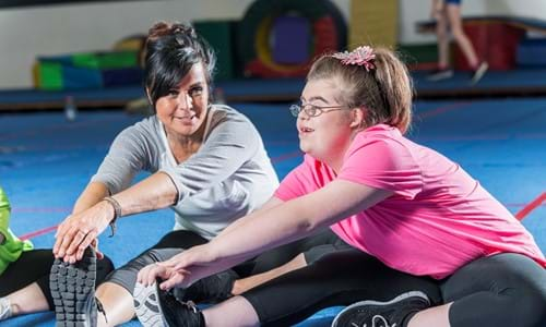 disabled girl stretching with her dance teacher