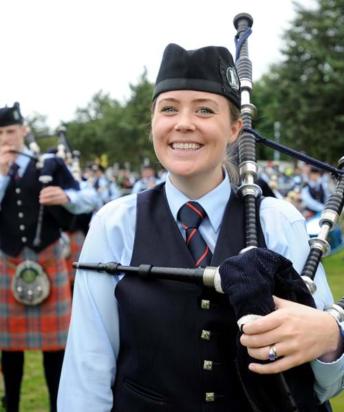 Female bagpiper smiles to camera.