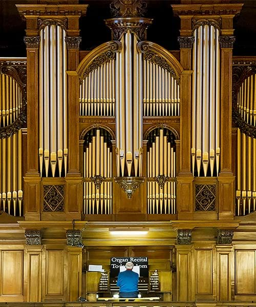 The Kelvingrove organ - the organ is large and ornate. A man is sitting and playing the organ.